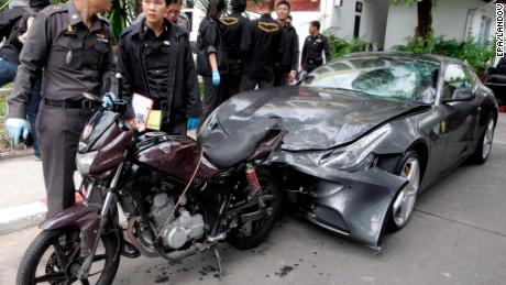 Thai police officers inspect a Ferrari car on September 3, 2012.