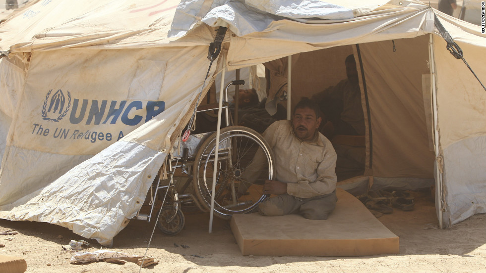 A handicapped Syrian refugee looks out of his tent. Za'atari Camp was built on a barren desert plain without a tree or shrub in sight. Severe sandstorms and scorching heat have taken their toll on refugees and aid workers here.