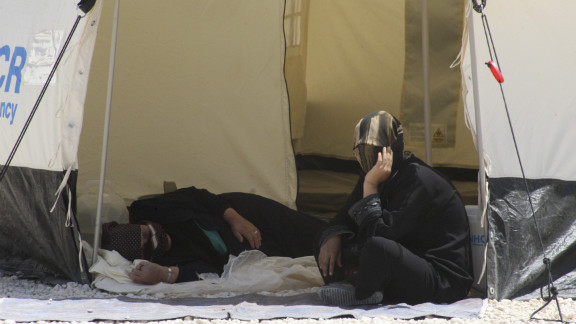 Syrian refugees look out from their tent.