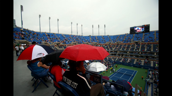 Spectators shelter under umbrellas as rain delays play during the women