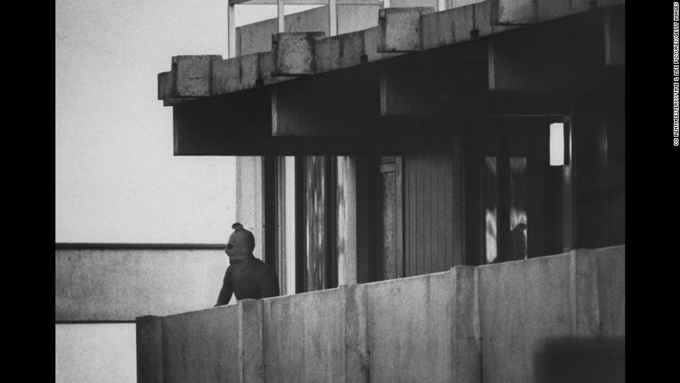 A Black September terrorist looks from the balcony of an apartment where Israeli Olympic team members are held hostage, Munich, September 1972.