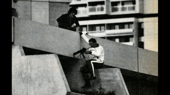Perched on a terrace directly above the Israeli quarters, a German policeman checks his submachine gun before advancing further, Munich, September 1972.
