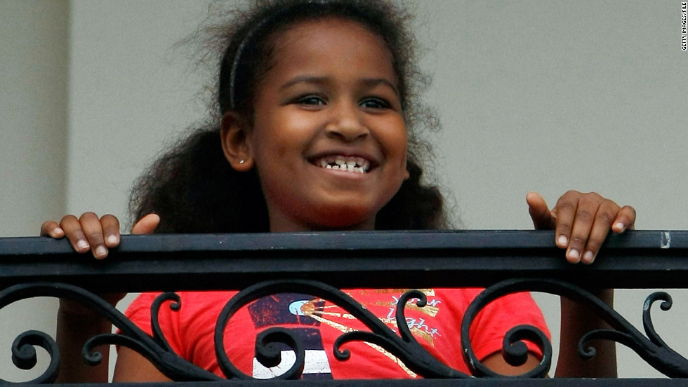 Sasha watches her dad from the Truman Balcony after he arrives on the South Lawn of the White House in May 2009.