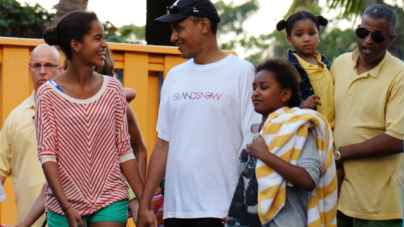 The President walks with his daughters after a visit to Sea Life Park in Hawaii in December 2011.
