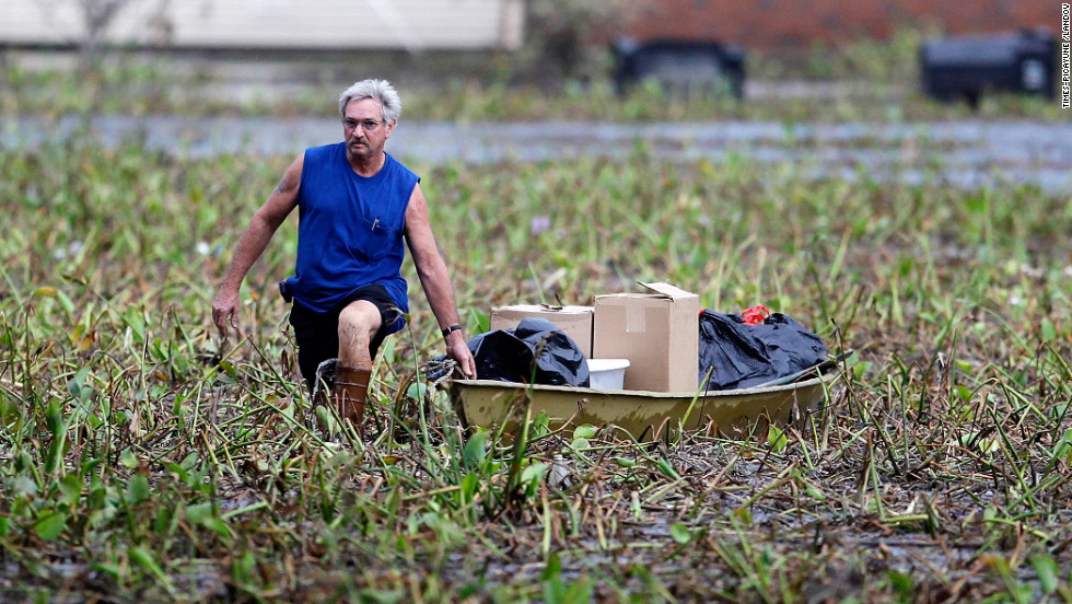 Richard Williams of the Braithwaite neighborhood in Plaquemines Parish, Louisiana, trudges through a debris field pulling a boat filled with things from his flooded home on Wednesday. Hurricane Isaac inundated his two-story home.