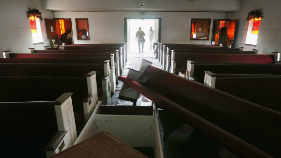 An insurance inspector tours the damaged Bethlehem Baptist Church on Tuesday.