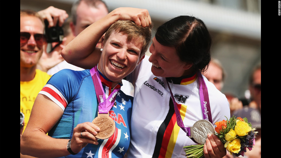 Bronze medalist Allison Jones, left, of the USA celebrates with silver medalist Denise Schindler of Germany after the women's individual C1-3 road race on Thursday.
