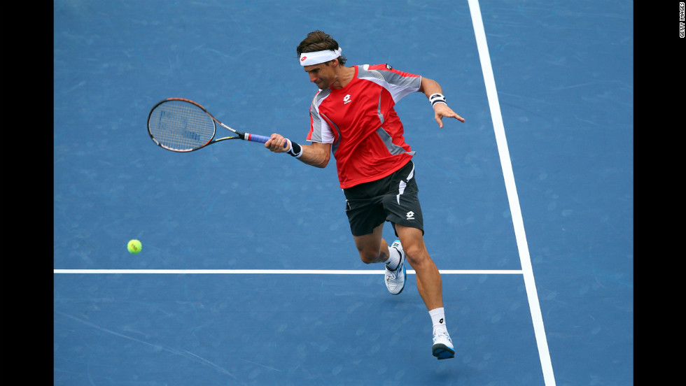 Ferrer returns a shot against Tipsarevic during their quarterfinal match.