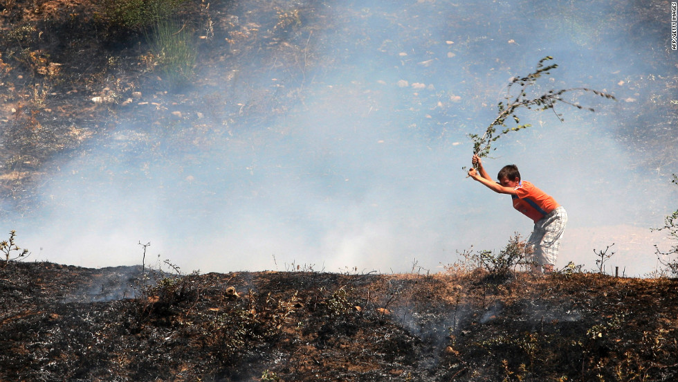 An Albanian boy uses a branch to try to put out a blaze near the city of Memaliaj, Albania, on August 28, 2012. Albania has battled multiple forest fires since June after several heat waves and months of drought. <br />