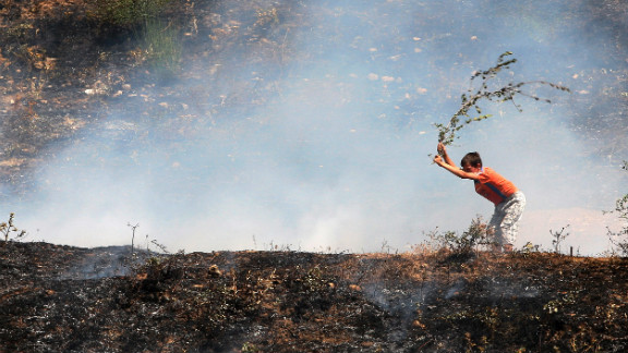 An Albanian boy uses a branch to try to put out a blaze near the city of Memaliaj, Albania, on August 28, 2012. Albania has battled multiple forest fires since June after several heat waves and months of drought.