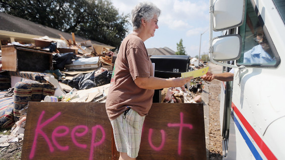 Marie Hauser picks up her mail outside her flooded house Thursday in LaPlace, Louisiana.