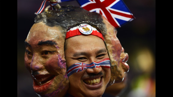 A spectator from Thailand wears masks as he watches Thursday