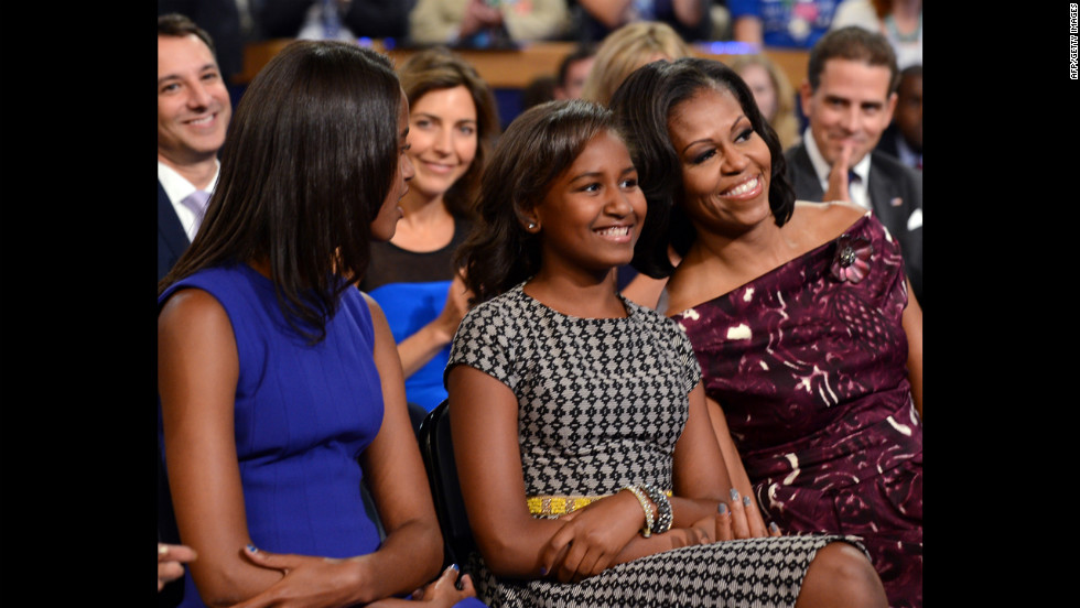 First lady Michelle Obama, with daughters Malia, left, and Sasha, smiles as Barack Obama delivers his acceptance speech on Thursday.