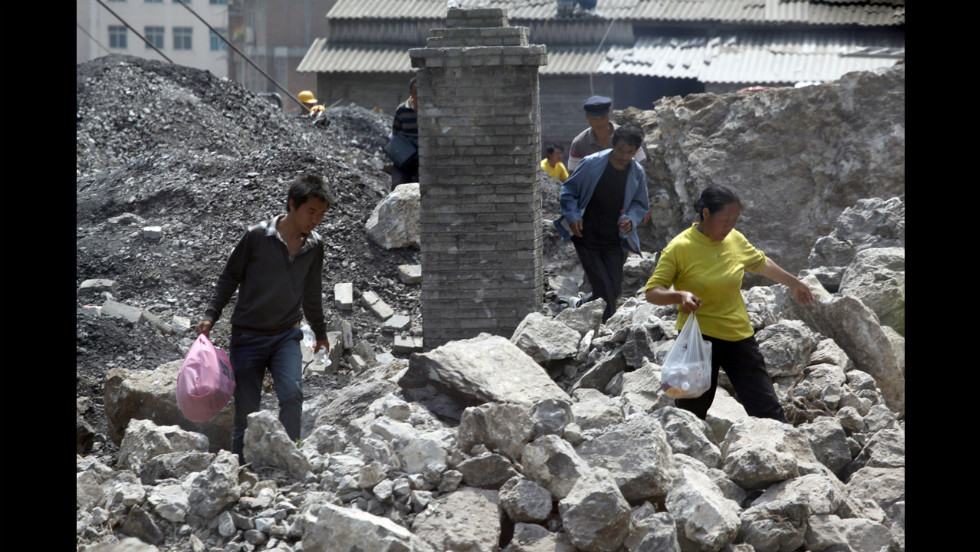 Survivors make their way through the rubble of a collapsed home on Saturday.