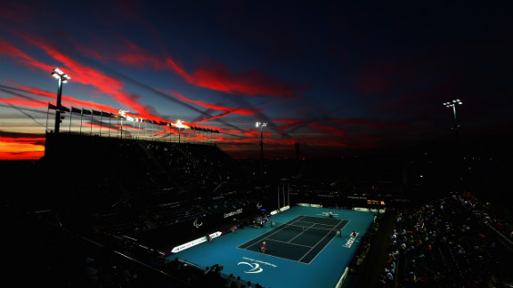 The sun sets as Shingo Kunieda of Japan, front left, plays against Stephane Houdet of France in the men