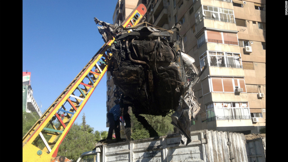Syrian workers remove damaged vehicles from the site where a booby-trapped car exploded in the suburb of Mazzah, Damascus, on Friday. According to media reports, one person was injured in the explosion, which caused material damage to the area.