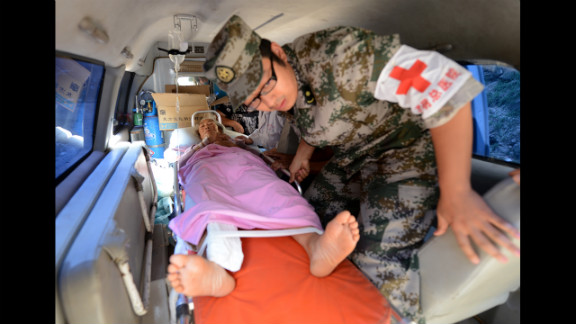 A woman is loaded into an ambulance Sunday after being injured in a landslide following a series of earthquakes.