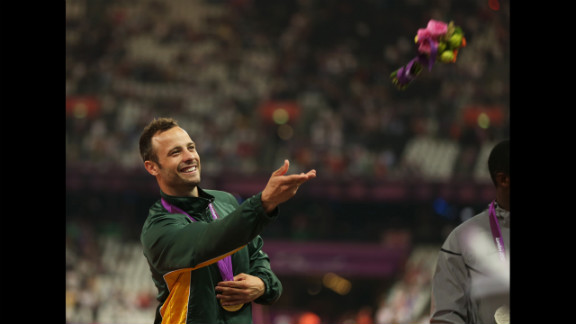 Gold medalist Oscar Pistorius of South Africa throws a bouquet of flowers on the podium during the medal ceremony for the men