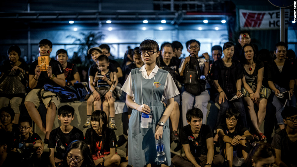 A student looks on as protesters sit near the government's headquarters in Hong Kong. Demonstrators demanded that the government scrap plans to introduce a compulsory Chinese civic education subject, which it the same evening.