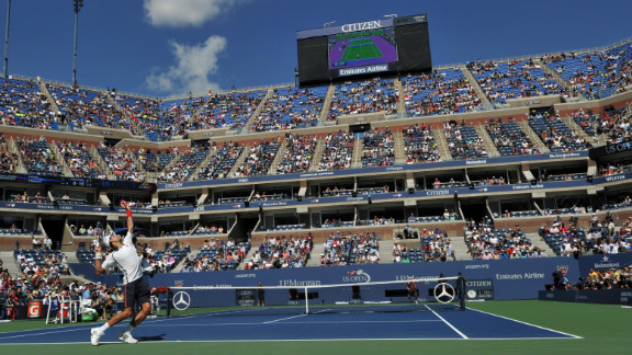 Djokovic serves to Ferrer as their match resumes Sunday after being delayed Saturday because of inclement weather.