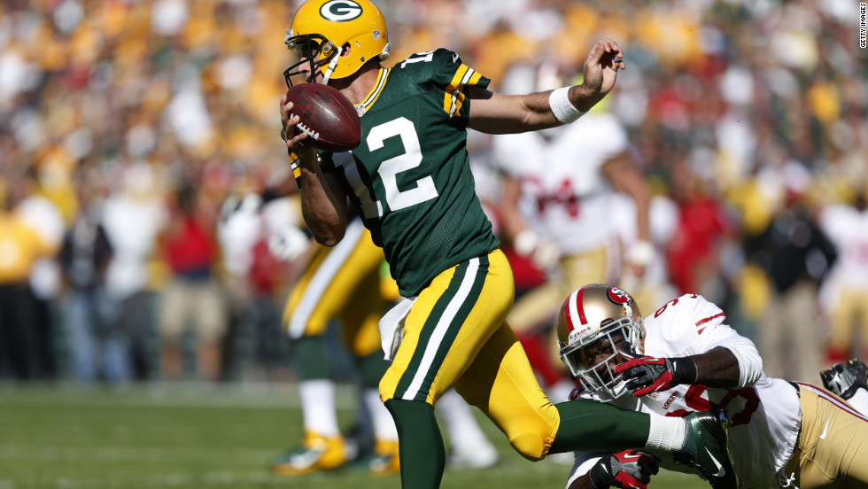 No. 12 Aaron Rodgers of the Packers runs away from pursuit by No. 99 Aldon Smith of the 49ers in the first half of the game on Sunday.