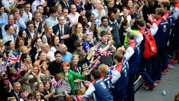 Members of Team GB greet spectators as the Victory Parade passes along Fleet Street, London.