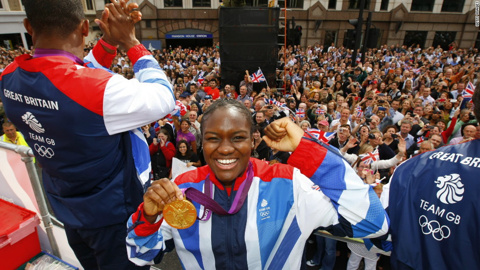 Olympic boxer Nicola Adams smiles as she holds up her gold medal for the camera.