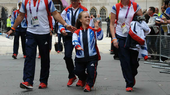 """Swimmer Eleanor Simmonds, known as """"Ellie"""", waves to the crowds as she walks along during the Victory Parade. Simmonds won two gold medals and a silver at the Paralympics."""