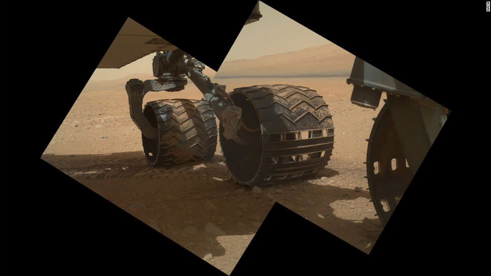 "This view of the three left wheels of NASA's Mars rover Curiosity combines two images that were taken by the rover's Mars Hand Lens Imager on September 9, 2012, the 34th day of Curiosity's work on Mars. In the distance is the lower slope of ""Mount Sharp."""