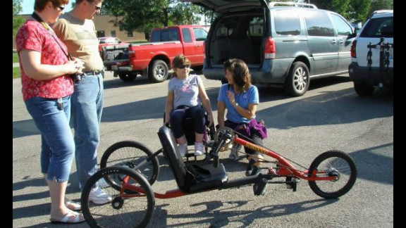 Alice Teisan has had chronic fatigue syndrome for the past 20 years. An avid cyclist who can no longer cycle, she founded His Wheels International in 2005 to help provide transportation to those in need. Here, parents Kern and Dawna Lunde watch physical therapist Nancy Biedry coach their daughter Anika, who is paralyzed from the waist down, as she learns to use her new trike prototype.