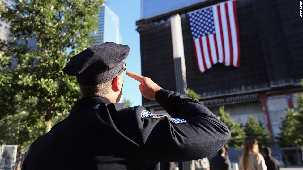A New York City police officer salutes a flag hanging from One World Trade on Monday.