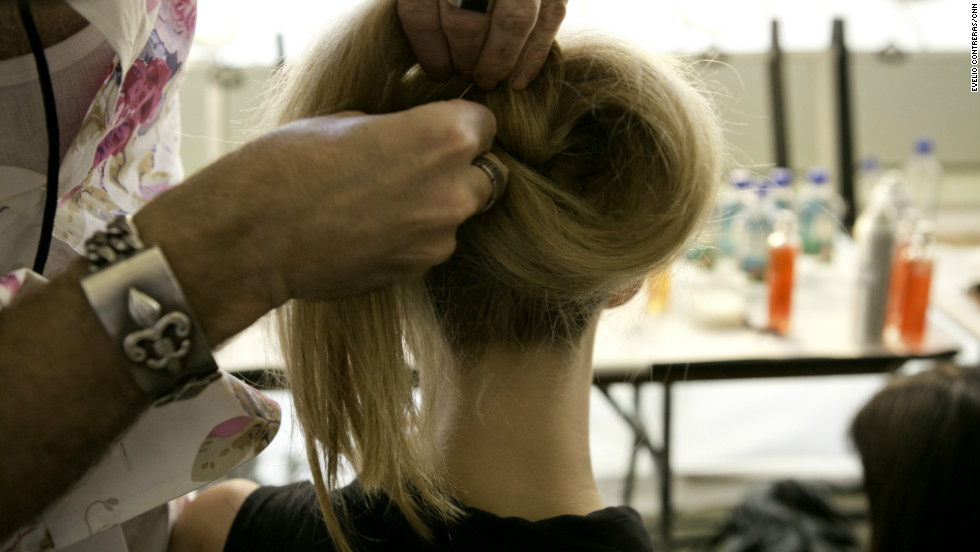 From here, take the right side of the hair and coil it clockwise around the base of the ponytail, tucking it into the elastic band after a full rotation.