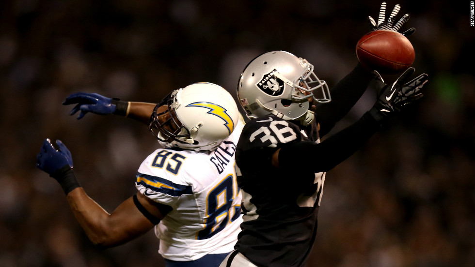 Shawntae Spencer of the Oakland Raiders tries, but fails, to intercept a pass intended for Antonio Gates of the San Diego Chargers.