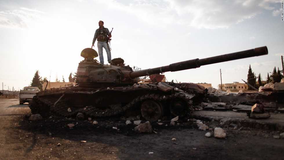 An armed fighter of the Free Syrian Army stands atop a destroyed Syrian army tank to have his picture taken by a passer-by in the northern Syrian town of Azaz, some 47 kilometers north of Aleppo, on Monday.