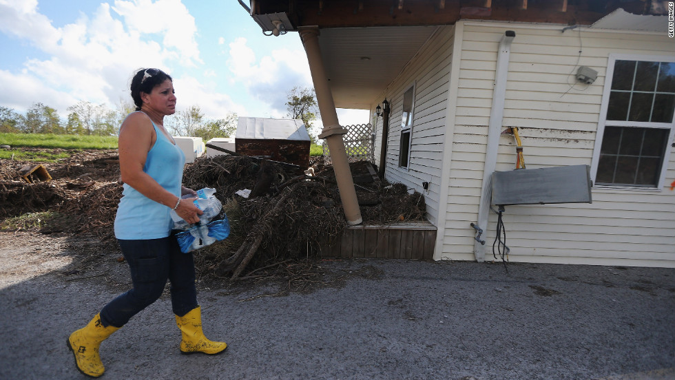 "On Friday, September 7, Gina Hunter walks past the front porch of her home, which washed onto a levee in Plaquemines Parish in Braithwaite, Louisiana.  ""I never expected to have the levee as my backyard,"" Hunter says. Louisiana officials estimate at least 13,000 homes were damaged by Hurricane Isaac."