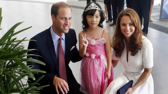 Prince William and Catherine pose with 4-year-old Maeve Low as they tour the Rolls-Royce Seletar Campus during the Diamond Jubilee tour at Seletar Aerospace Park on Wednesday, September 12, the second day of their Diamond Jubilee tour in Singapore.