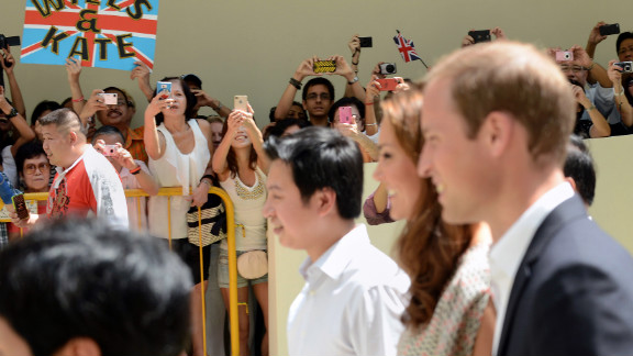 Bystanders crane for photos of the Duke and Duchess of Cambridge during their visit to Strathmore Green, a precinct in Queenstown, a residential district of Singapore on Wednesday.