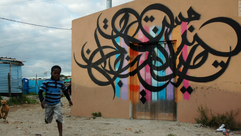 "During a recent visit to Cape Town, eL Seed defied advice to visit a township and paint on the wall of a newly constructed daycare building. He said there was a lot of debate among locals about his decision to write in Arabic. The words mean ""It is impossible unitl it is done."""