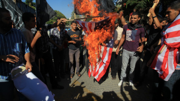 Palestinian men burn the American flag during Wednesday