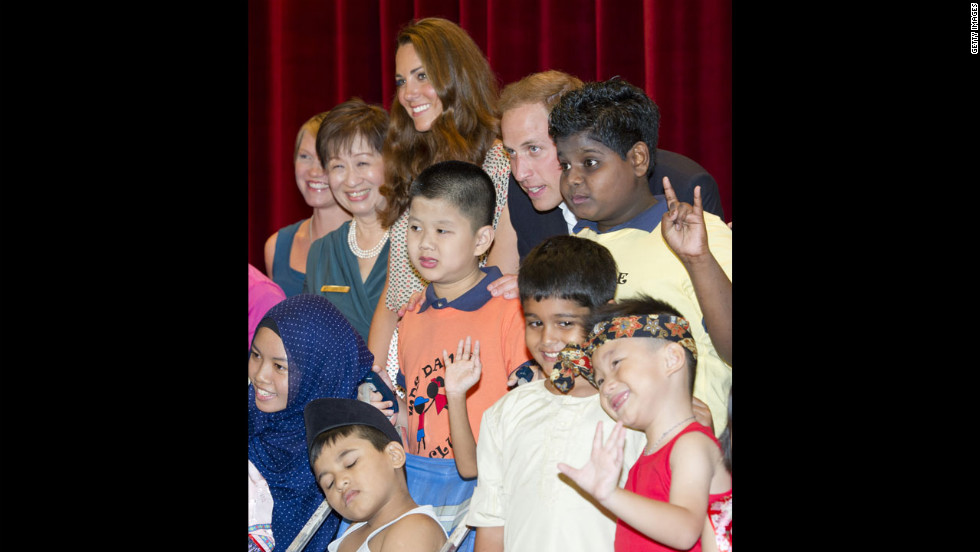 The duke and duchess pose for a picture with children as they visit The Rainbow Centre in Singapore.