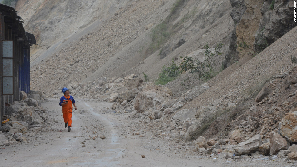 A man runs past a landslide area on Monday as high winds cause rocks to continue falling days after the earthquakes.