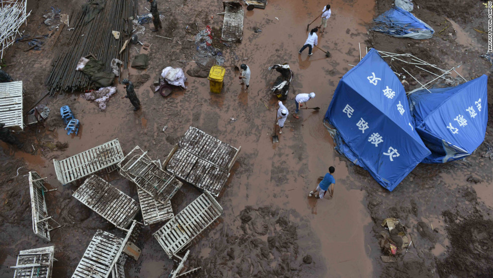 People clean up the mess after a mudslide hit a temporary hospital on Monday.