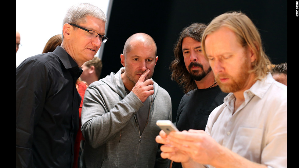 Apple CEO Tim Cook, left; Jonathan Ive, senior vice president of industrial design; and Dave Grohl of the Foo Fighters watch Foo Figters' bassist, Nate Mendel, handle the iPhone 5.