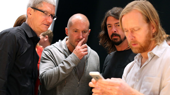 Apple CEO Tim Cook, left; Jonathan Ive, senior vice president of industrial design; and Dave Grohl of the Foo Fighters watch Foo Figters