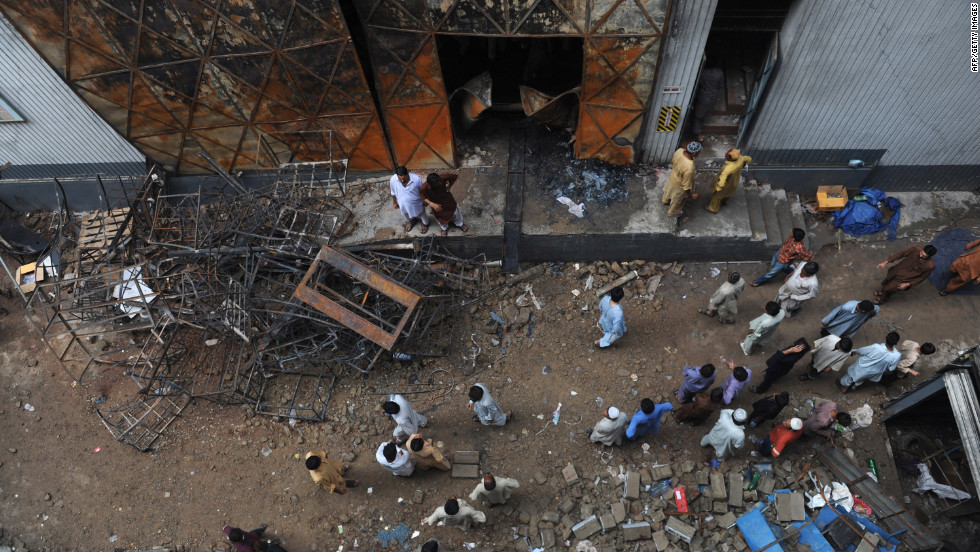 Pakistanis gather in Karachi in front of a garment factory following a fire Tuesday in which at least 258 people died.