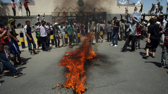 Yemeni protesters gather around a fire Thursday during a demonstration outside the U.S. Embassy in the capital of Sanaa.  Yemeni forces fired warning shots to disperse the thousands of protesters approaching the main gate of the mission.