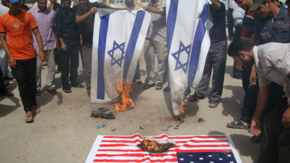 Iraqi protesters burn Israeli and U.S. flags during a protest Thursday.  The U.S. ambassador to Libya, J. Christopher Stevens, and three others were killed during a protest outside the U.S. Consulate in Benghazi, Libya, on Tuesday.