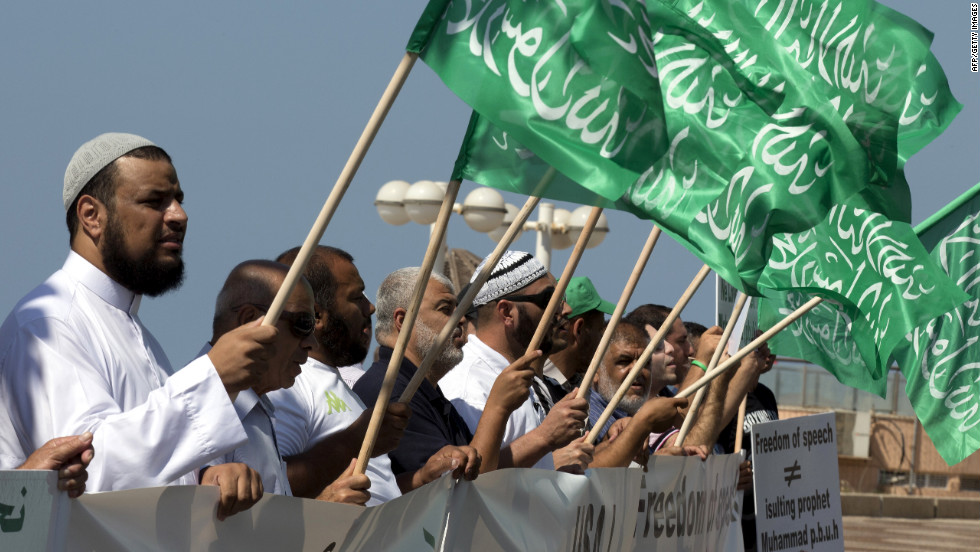 "Arab-Israeli men wave green Islamic flags with the Muslim profession of belief: ""There is no God but God and Mohammed is the prophet of God"" during a protest in front of the U.S. Embassy on Thursday in Tel Aviv, Israel."