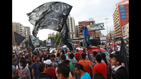 "Protesters carry flags that read ""There is no God but Allah, Mohammed is Allah"