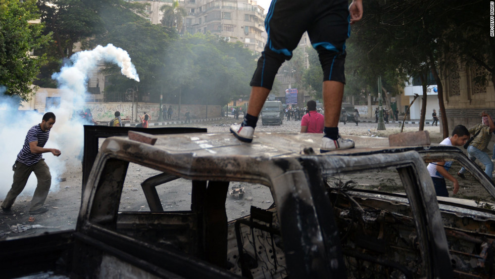Egyptian protesters run for cover from tear gas fired by riot police during clashes on Thursday.